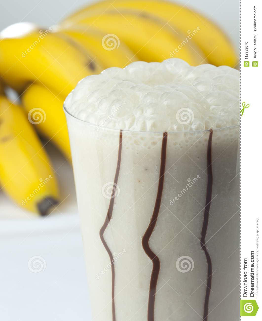 A glass of banana and milk cocktail close up with full fruits