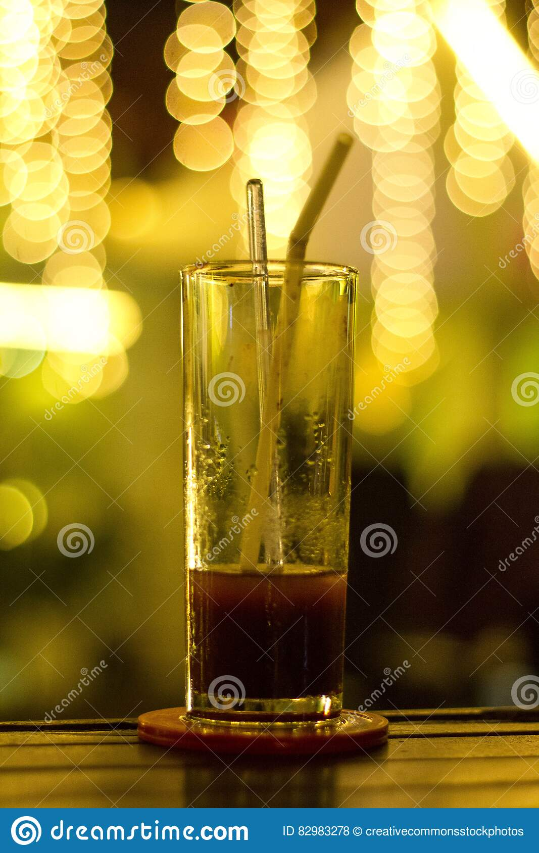 Glass on bar with red beverage