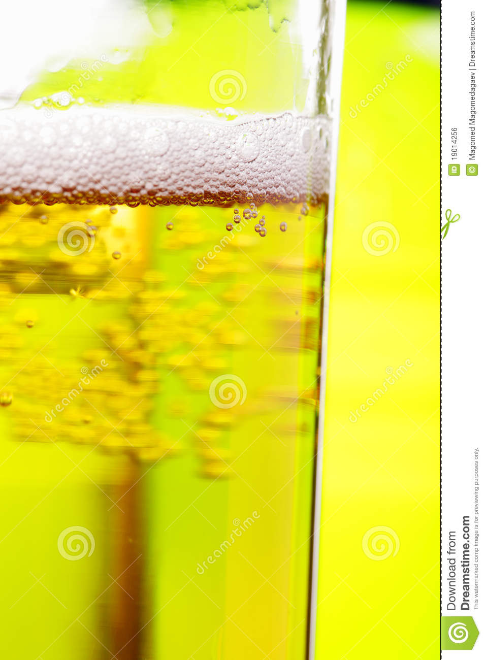 Glass of beer against green