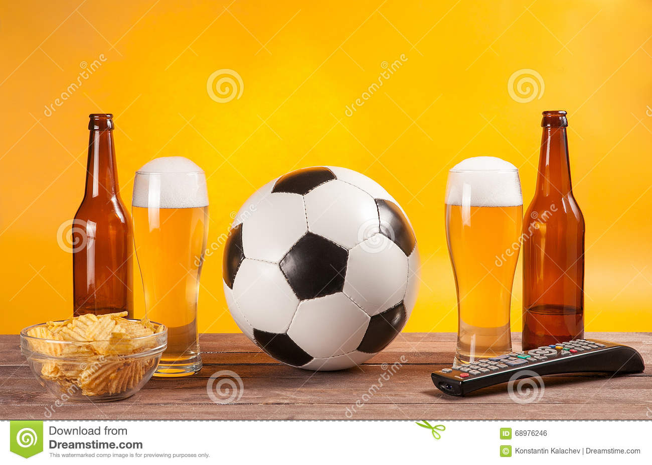 Glass with beer and soccer ball near tv remote
