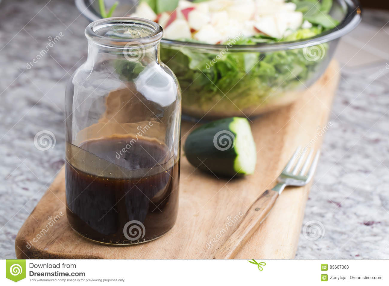 a glass bottle with salad dressing consisting of balsamic vinegar, honey and olive oil