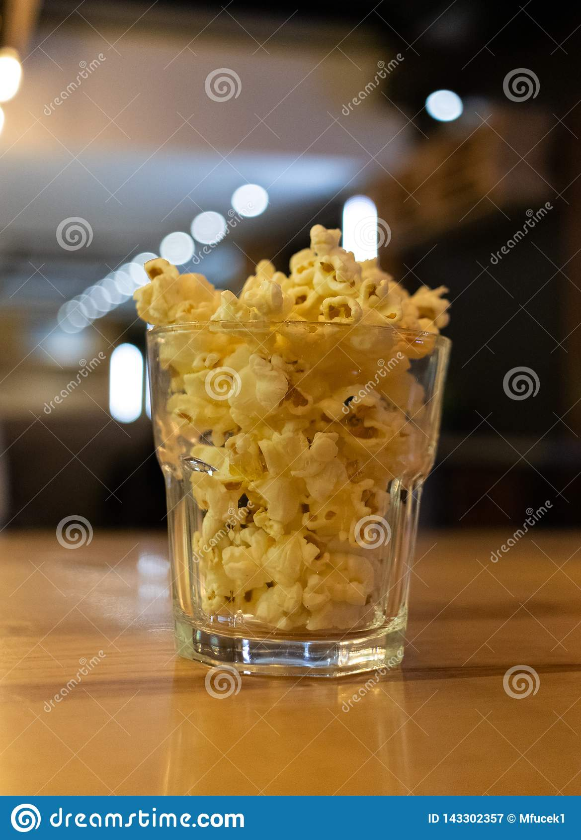 Glass bowl with tasty popcorn on table