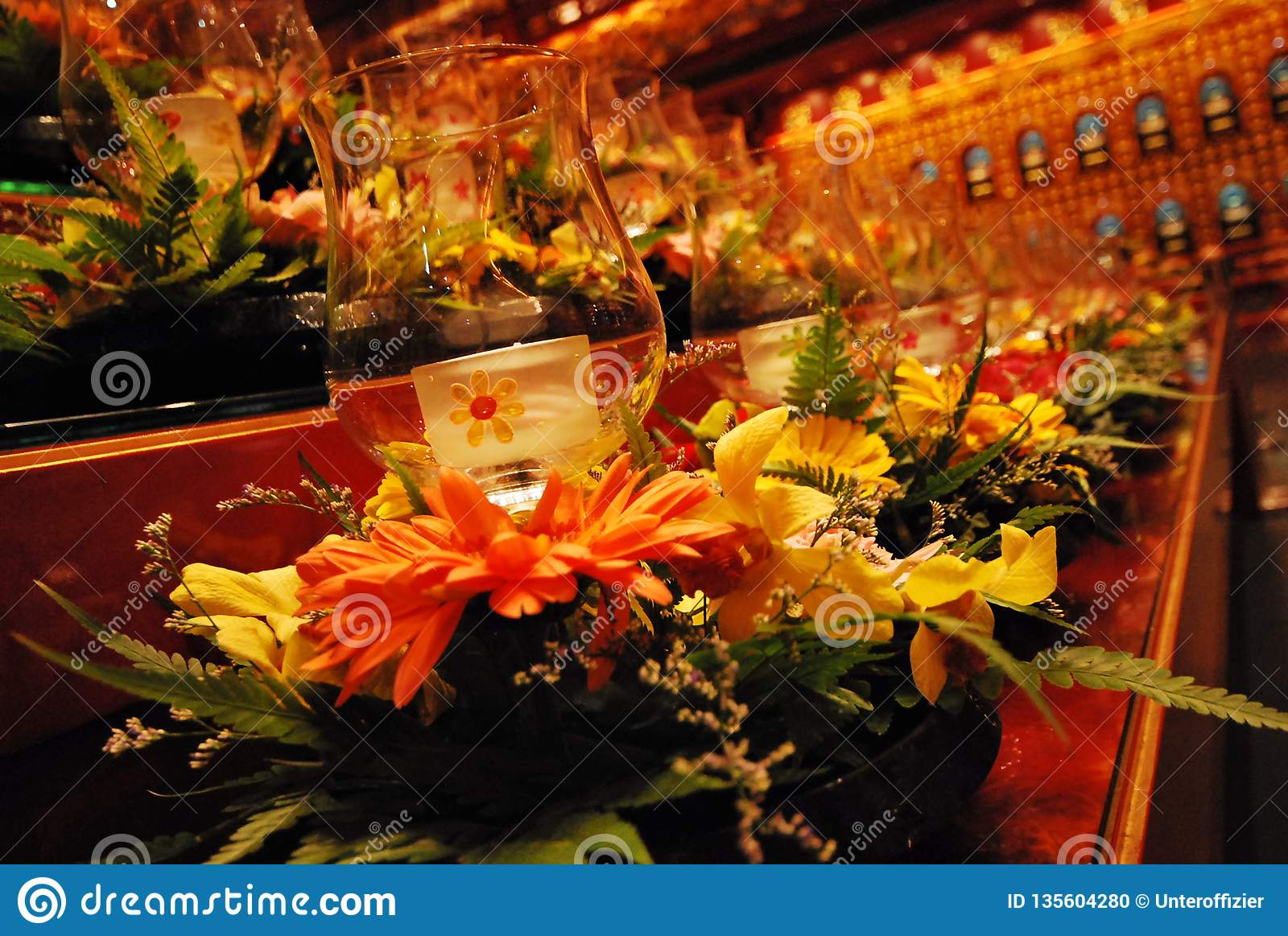 Glass candle holders at an altar bathed in amber interior lights