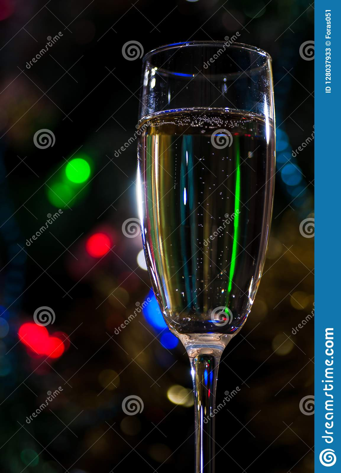 A glass of champagne under the Christmas tree on a dark background