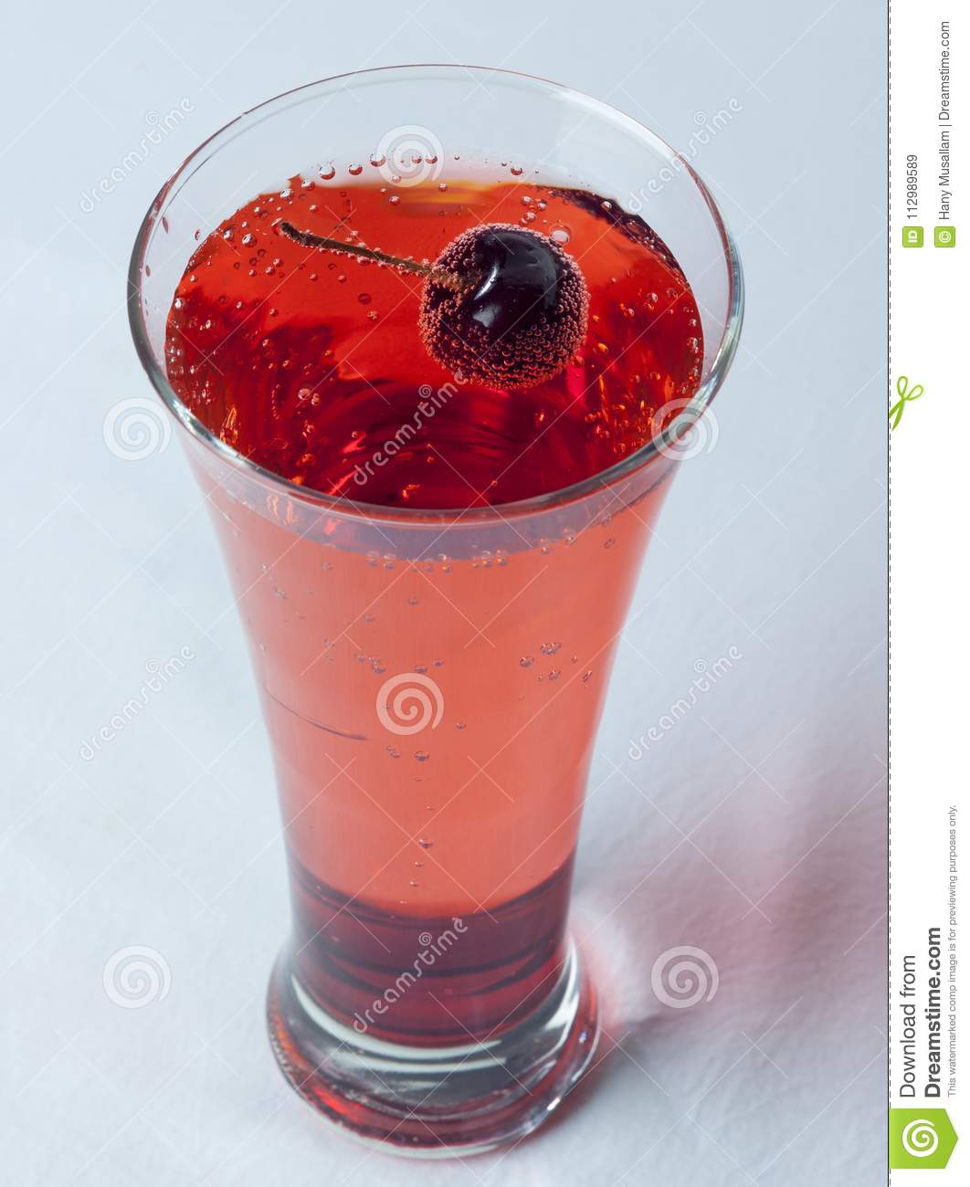 A glass of Cherry Juice close up with cherry fruit and Air Bubles