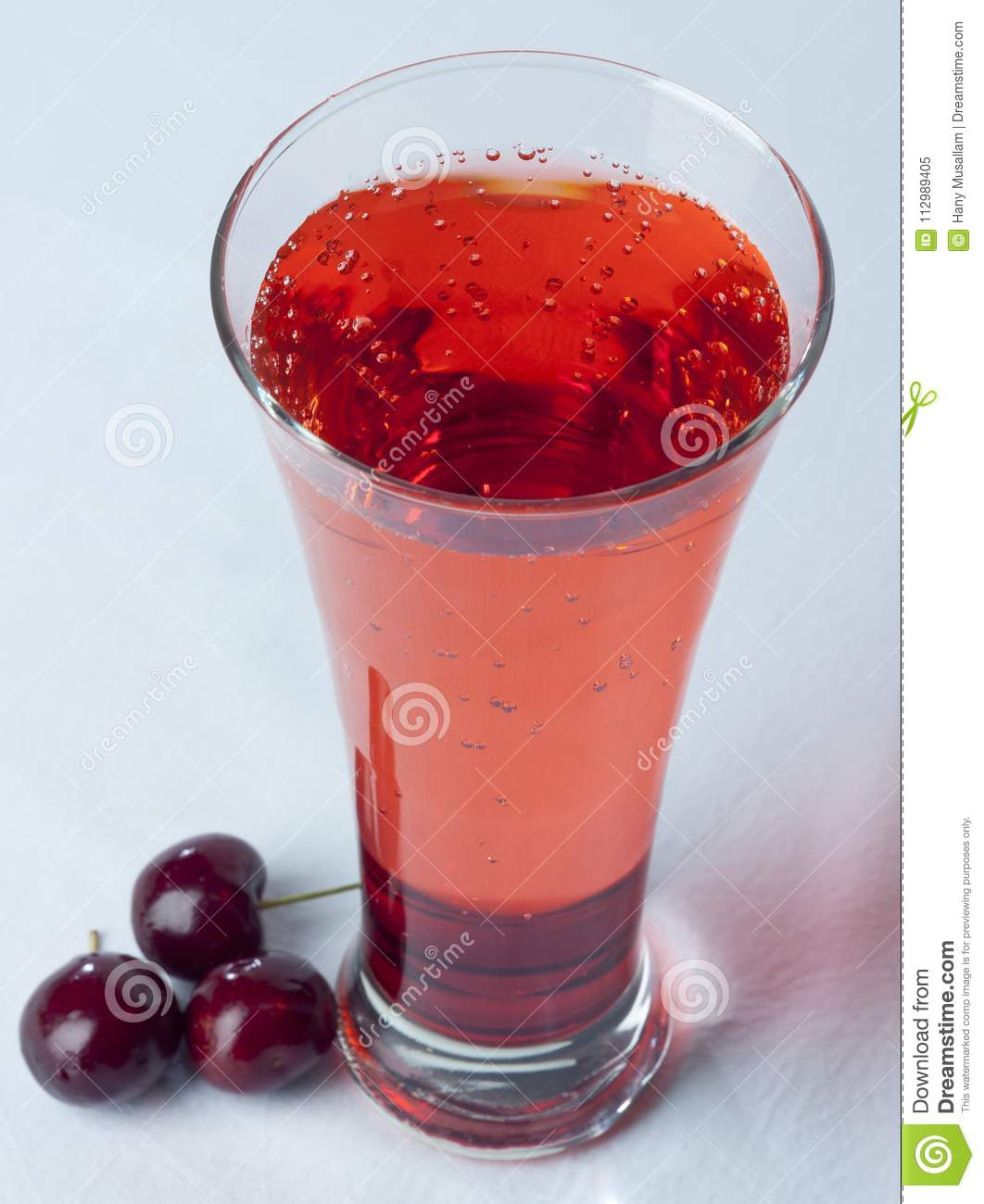 A glass of Cherry Juice close up with cherry fruit and Bubles