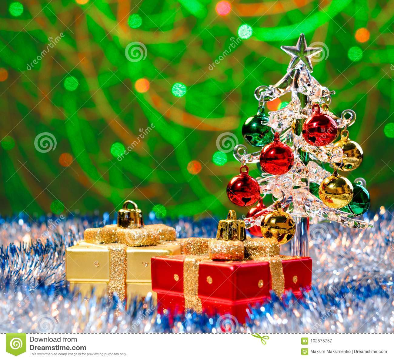 download glass christmas tree standing in the sparkling tinsel with christmas decorations on background with blurred