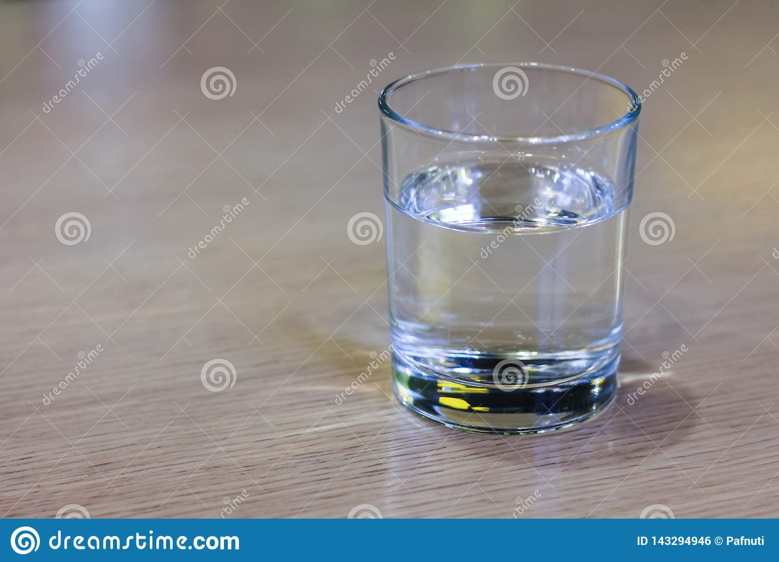 Glass of clear water on wooden table.