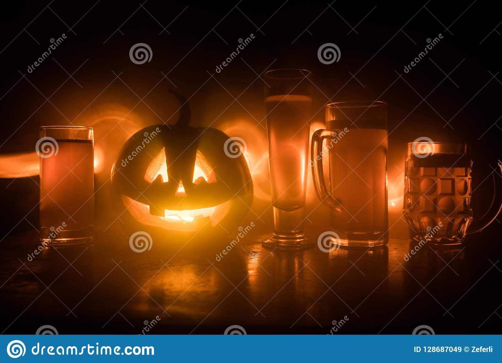 Glass of cold light beer with pumpkin on a wood background for Halloween. Glass of fresh beer and pumpkin on a dark toned foggy ba