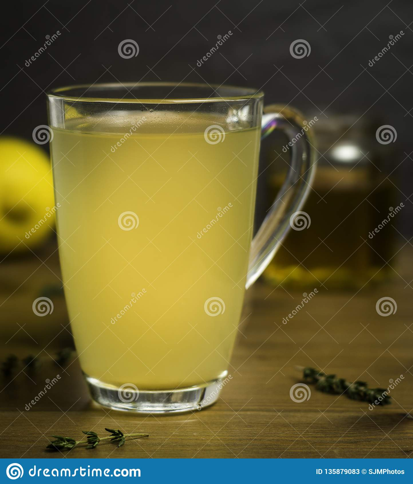 Glass Cup of Hot Lemon, Honey and Ginger Drink with sprigs of Thyme as a cold remedy