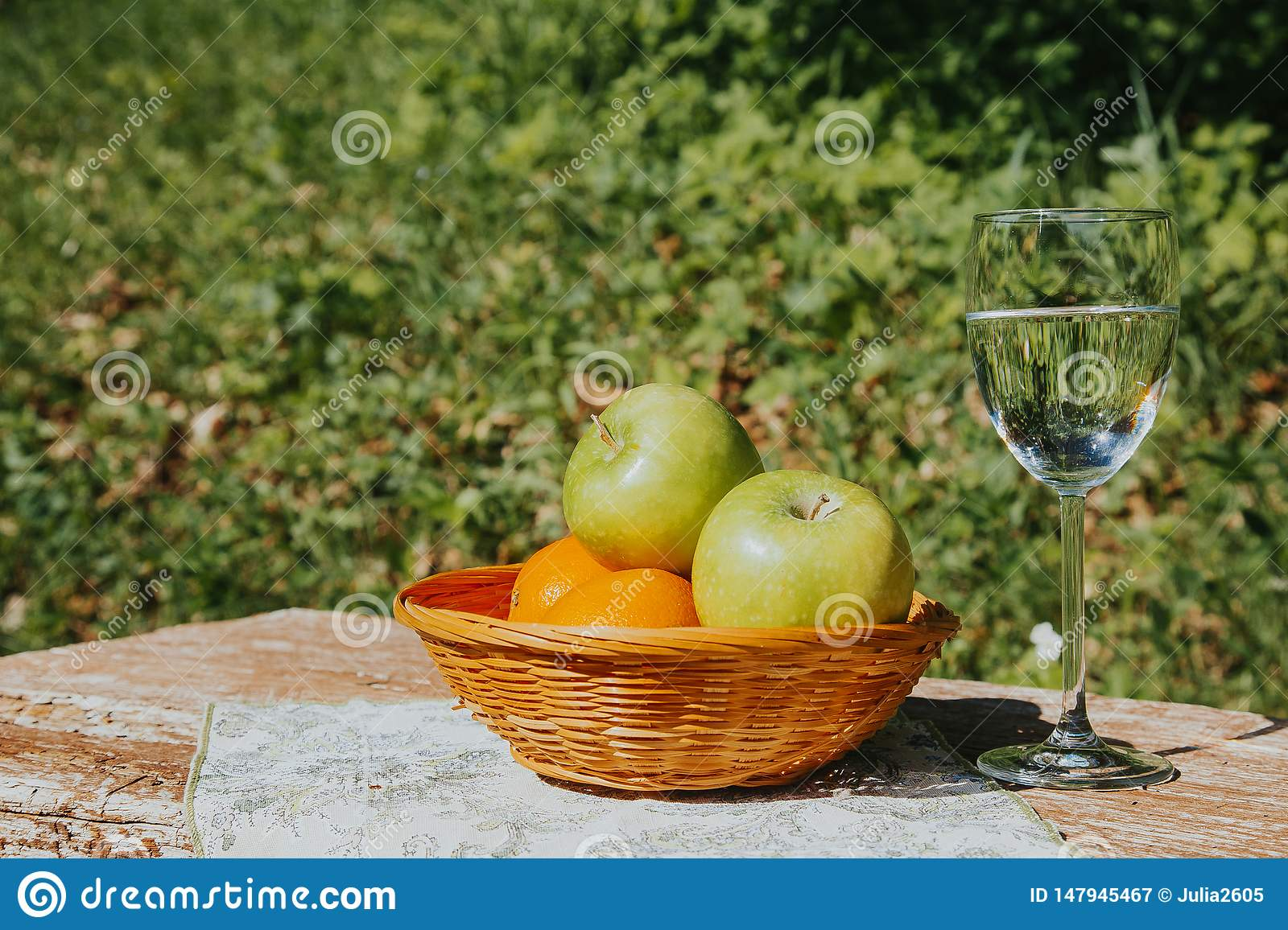 A glass of fresh Apple water and apples in a basket on a wooden table