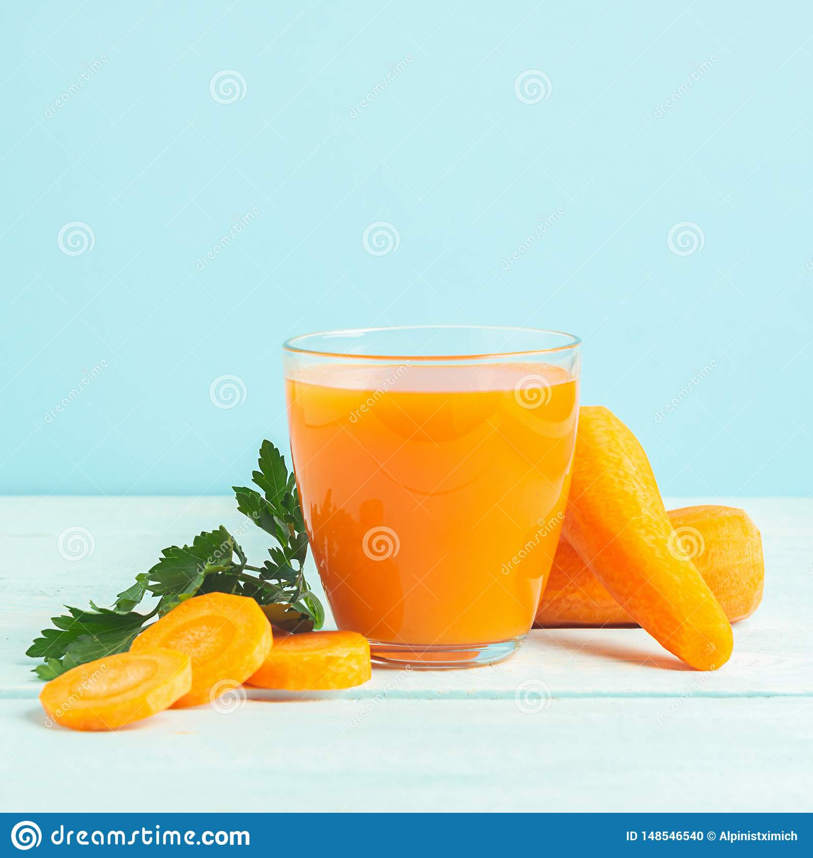 A glass of fresh carrot juice on a wooden blue background. Selective focus. Copy space