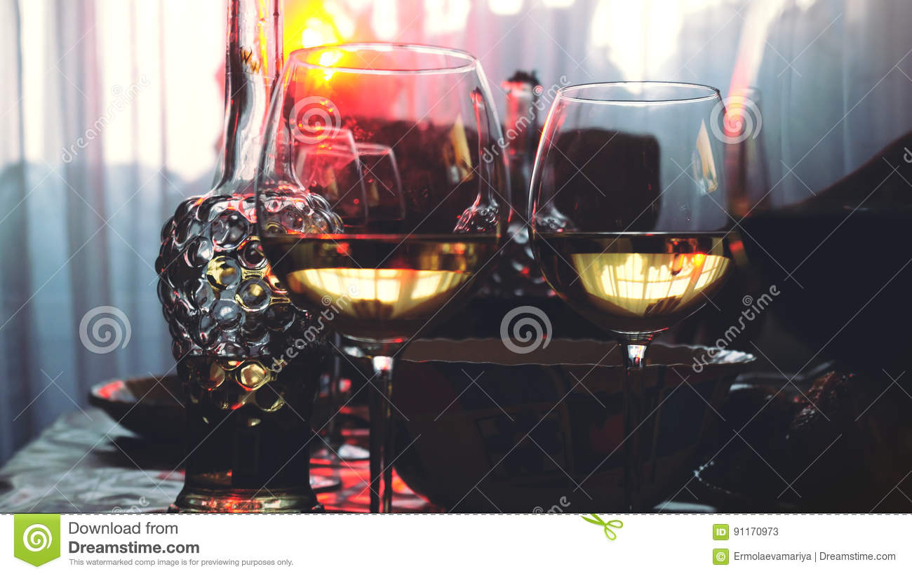 Glass glasses on a table in a restaurant, banquet table, glasses of wine stage red lighting.