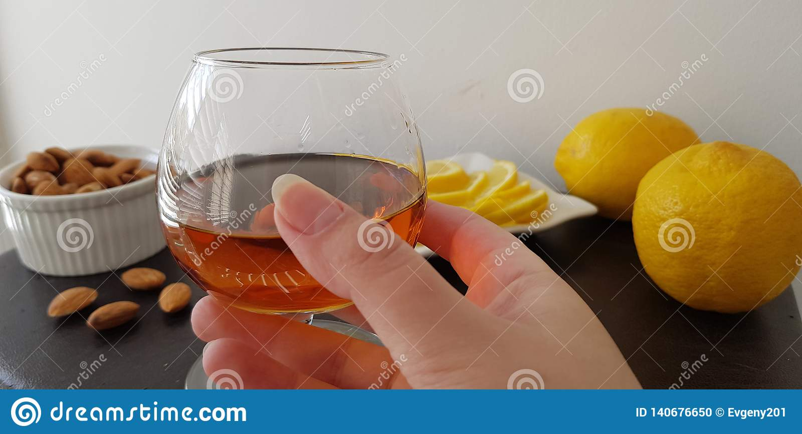 glass half full with brandy over brown table with almonds and lemons
