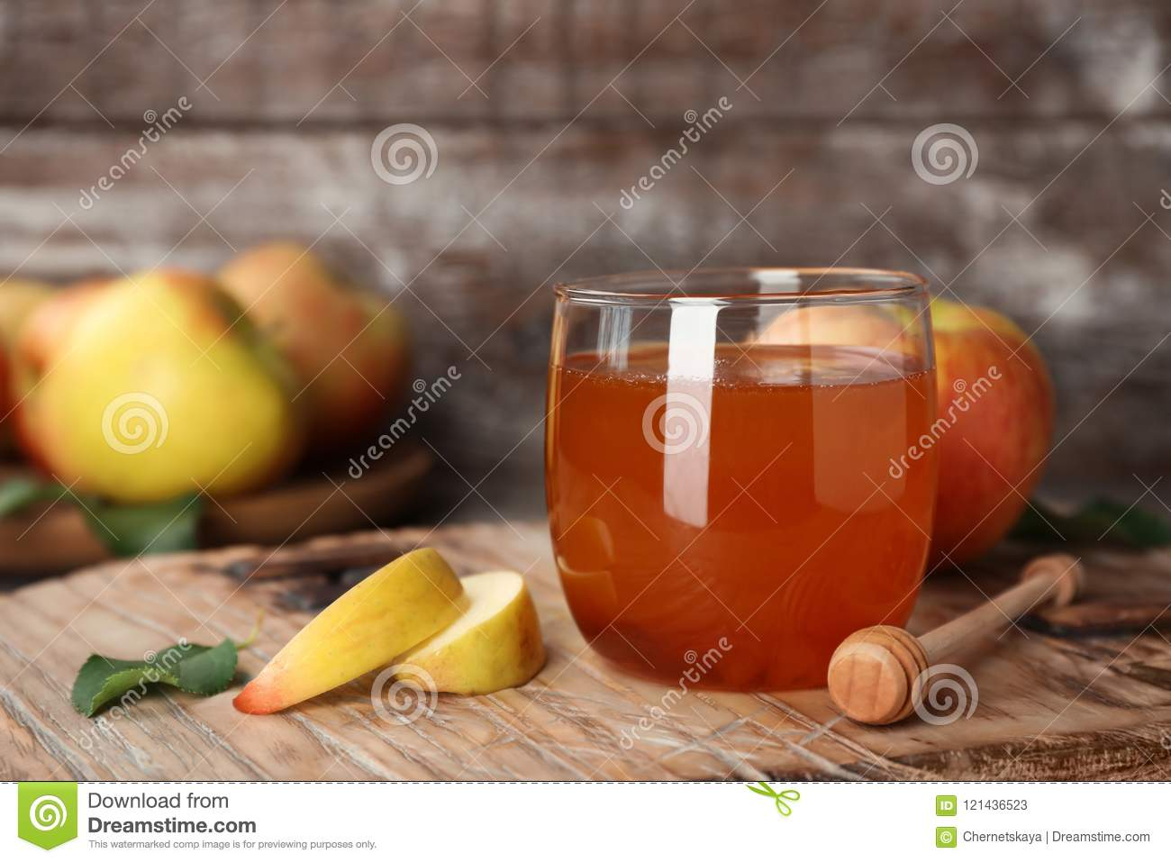 Glass of honey, apples and dipper