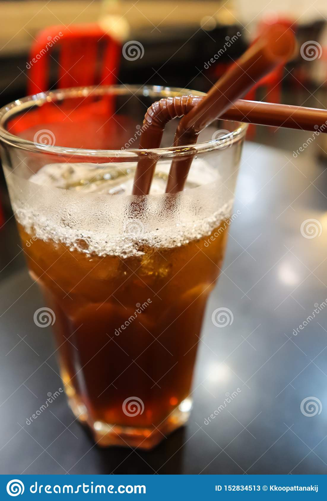 Glass of ice lemon tea with two brown straws on the black table in the restaurant. One glass for two, together. Concept image