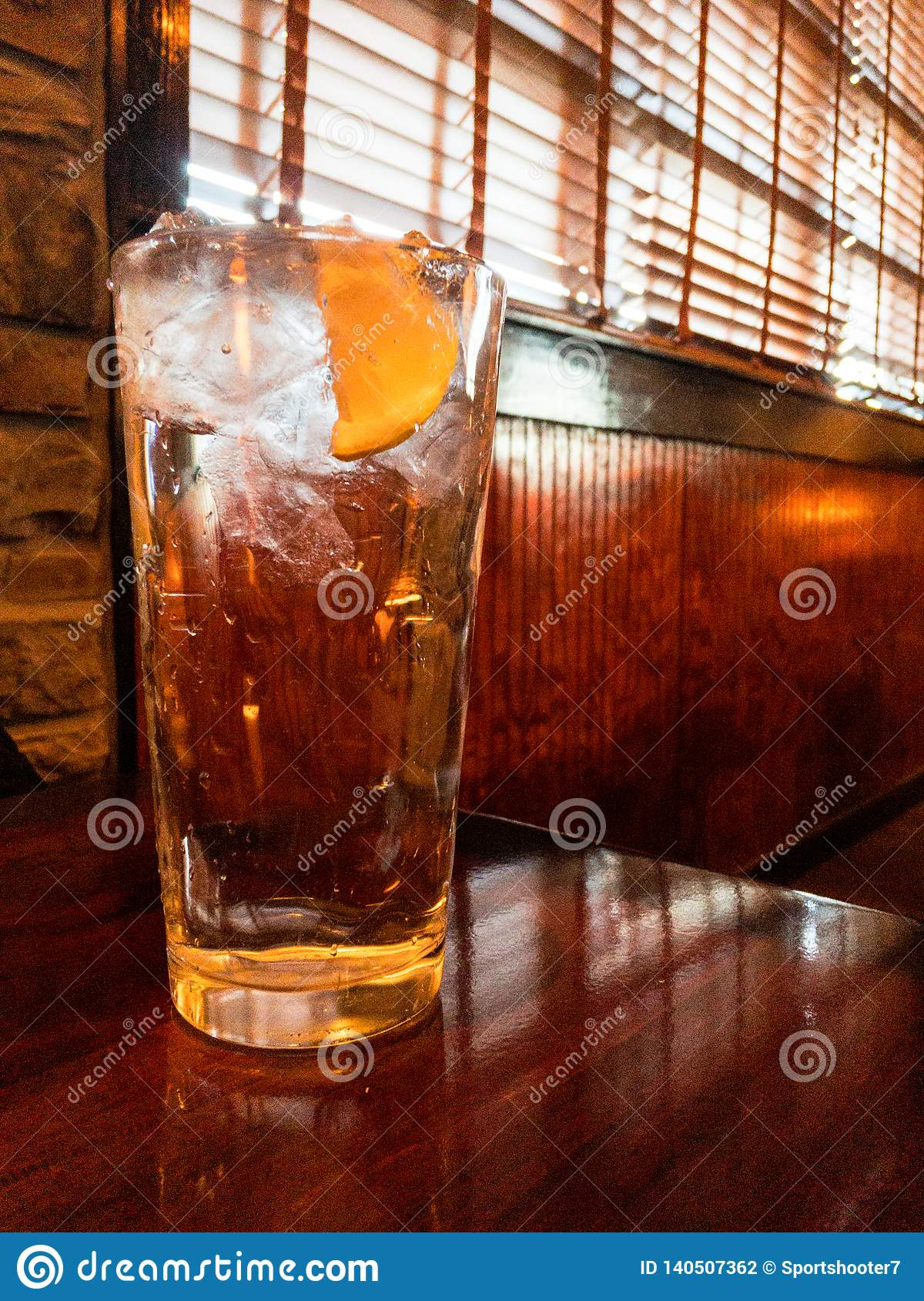 Glass of ice water with lemon on wooden table in restaurant setting. no people.