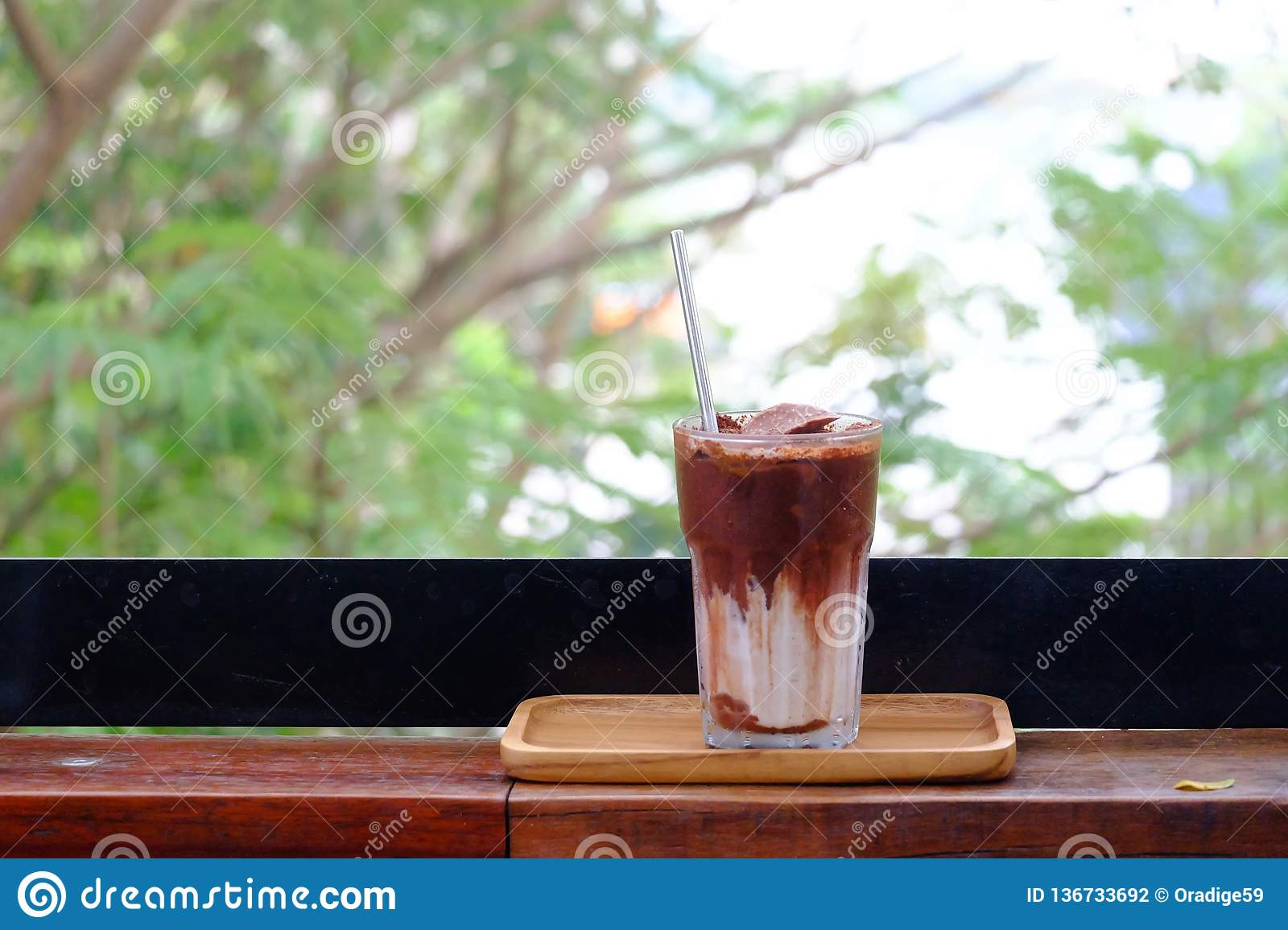 A glass of iced chocolate soft drinks with a steel straw in a wooden tray with an orange flower on wood balcony