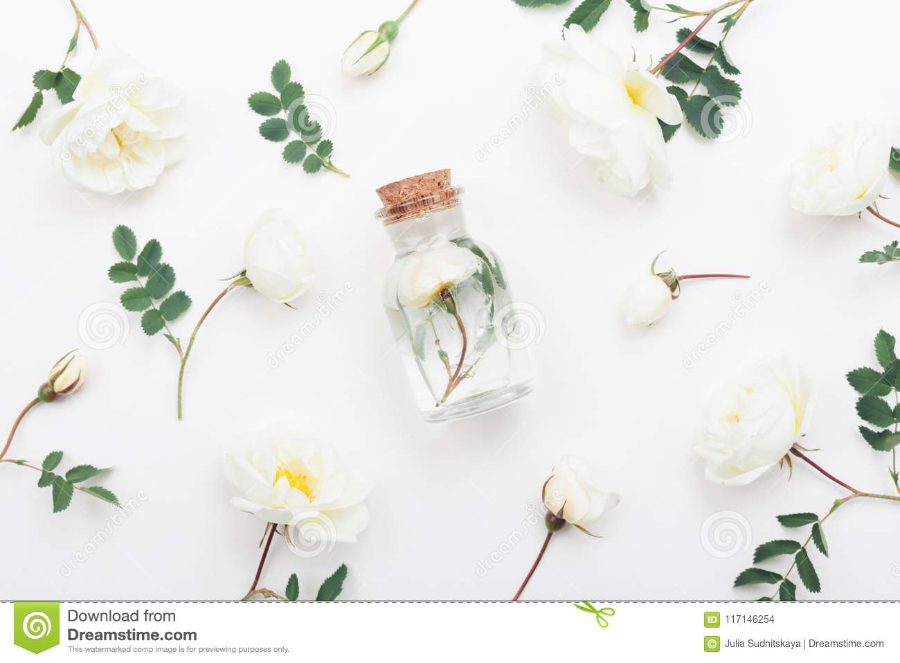 Glass jar with aroma water and beautiful rose flowers for spa and aromatherapy. Top view and flat lay style.