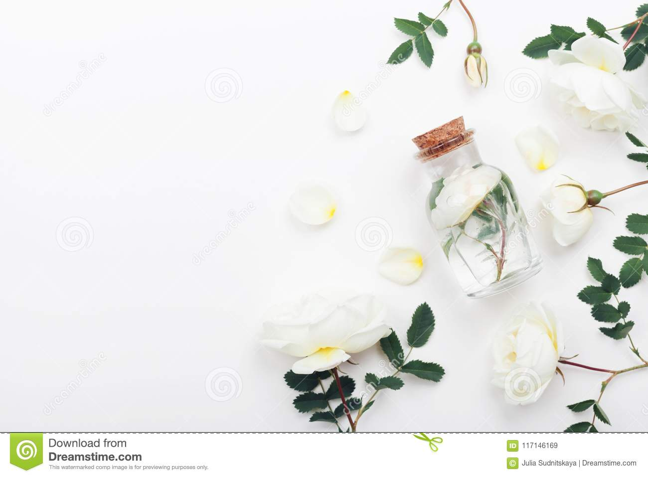 Glass jar with aroma water and white rose flowers for spa and aromatherapy. Top view and flat lay style.