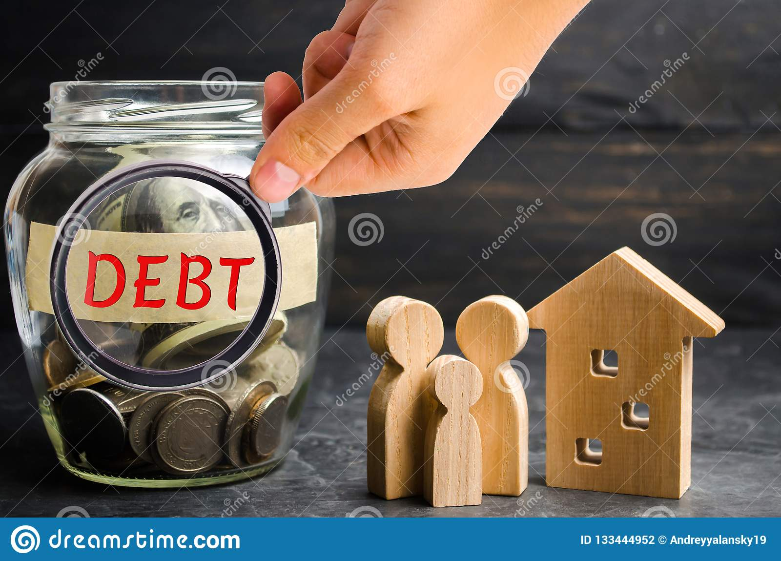Glass jar with coins and the inscription ` Debt `, family and wooden house. Real estate, home savings, loans market concept. Payme