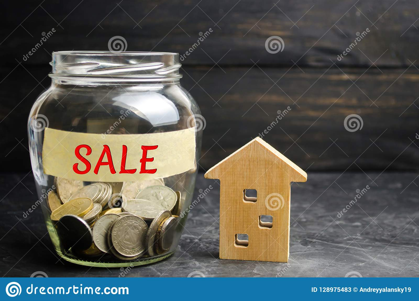 Glass jar with coins and the inscription `sale` and a small wooden house. real estate concept. sale of a home, apartment property