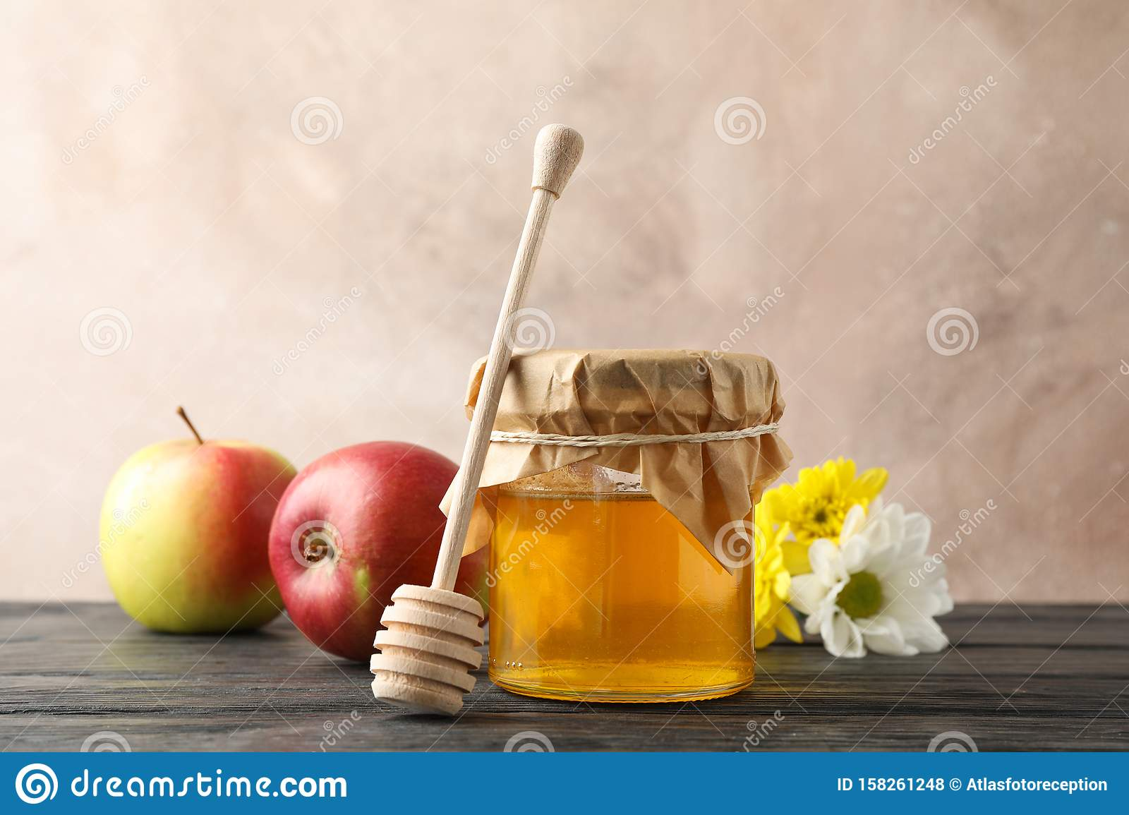 Glass jar with honey, dipper, apples and flowers on wooden background