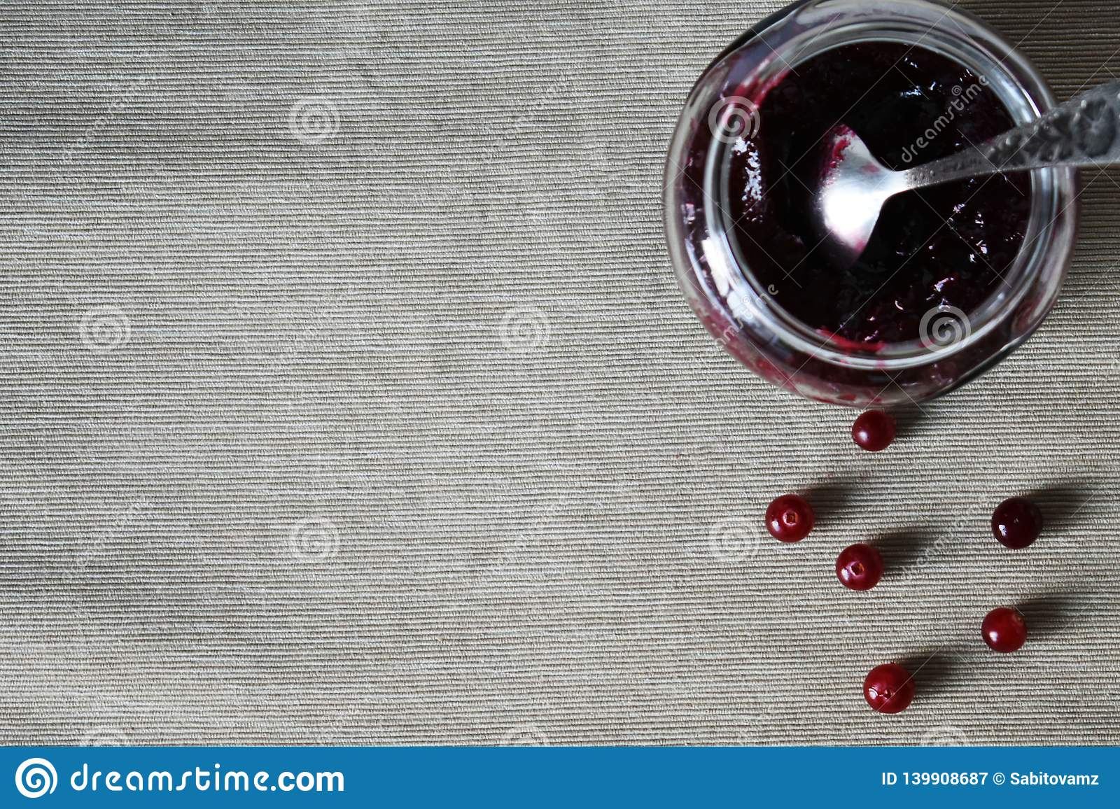 Glass jar with jam and cranberries on the table