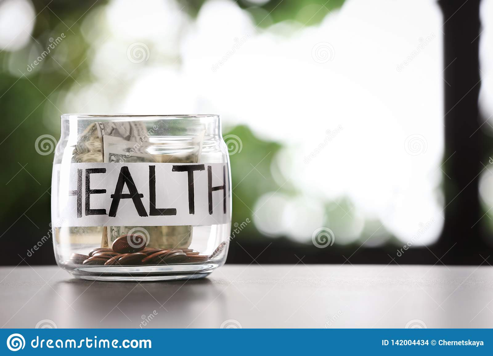 Glass jar with money and word HEALTH on table against blurred background