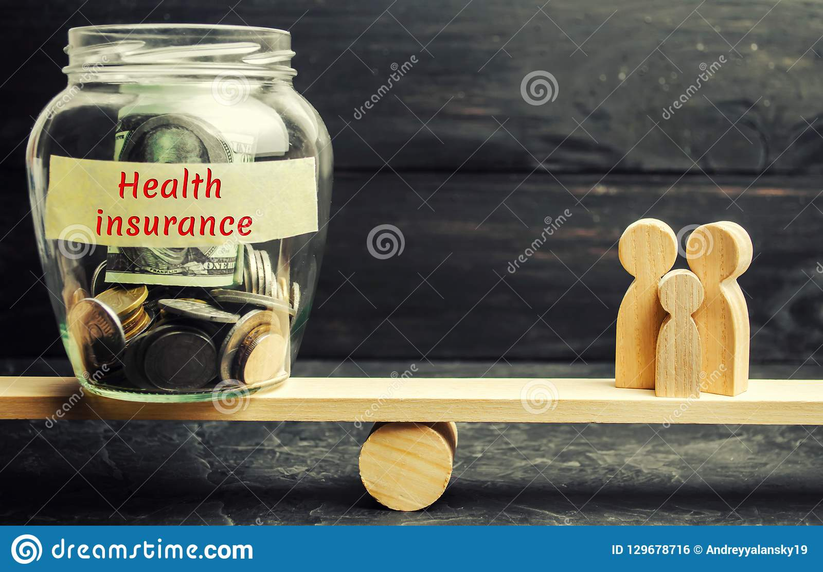 Glass jar with money and the words `Health Insurance` and the family on the scales. The concept of medical insurance of life, fami