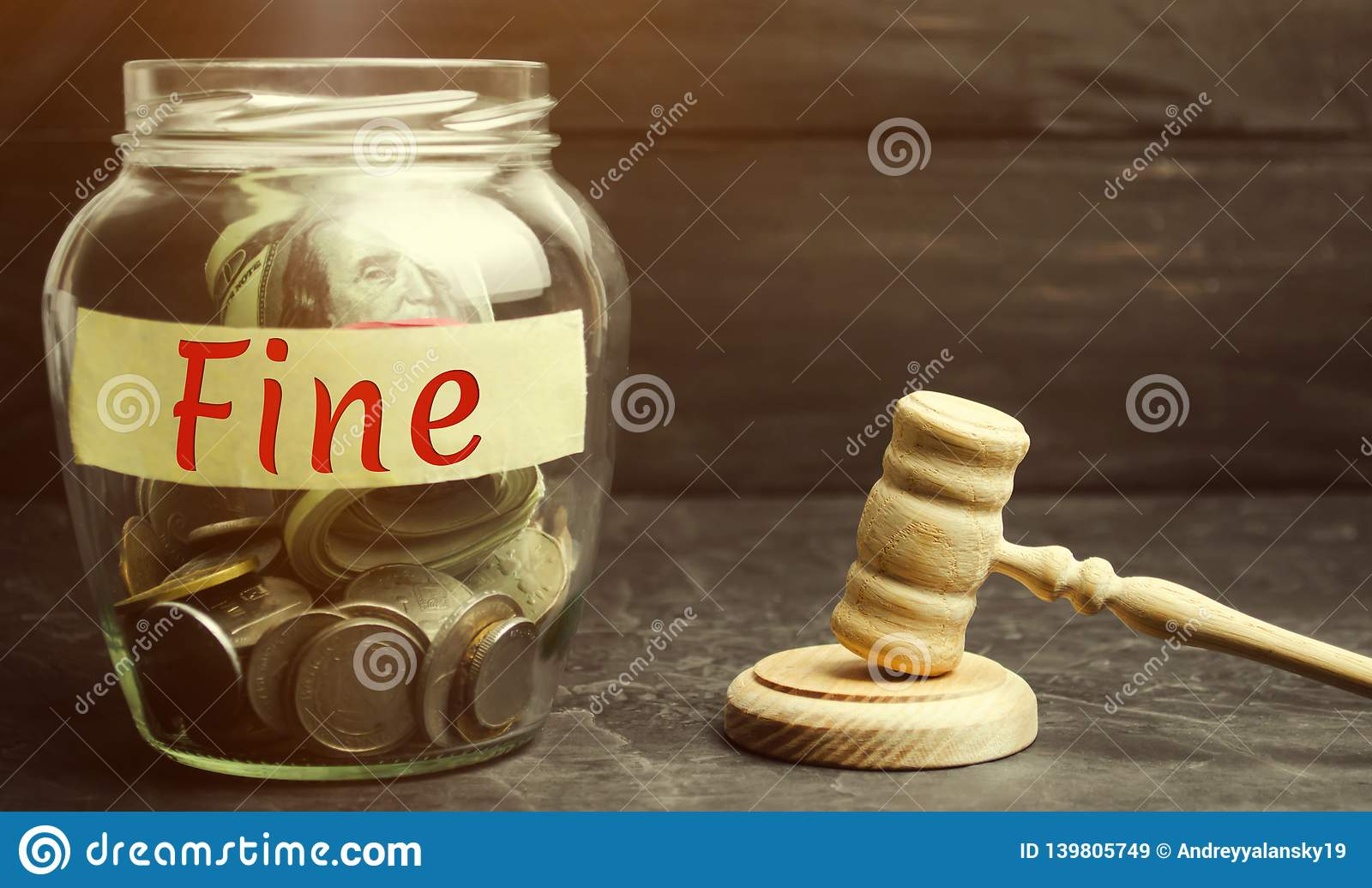 Glass jar with the word Fine and the judge`s hammer. Penalty as a punishment for a crime and offense. Financial punishment.