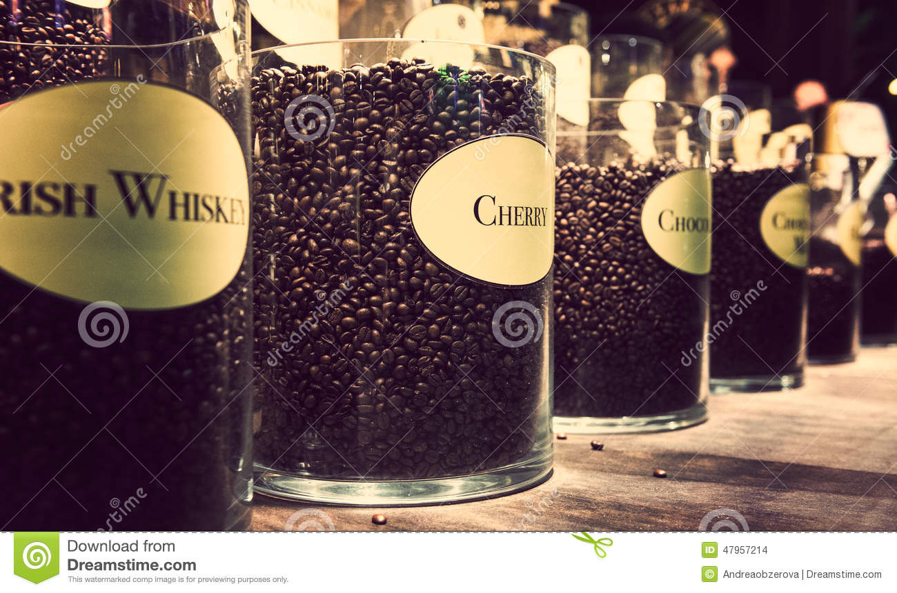 glass jars with different flavour coffee on display stock