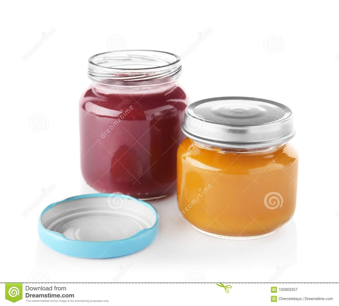 Glass jars with nutrient baby food on background