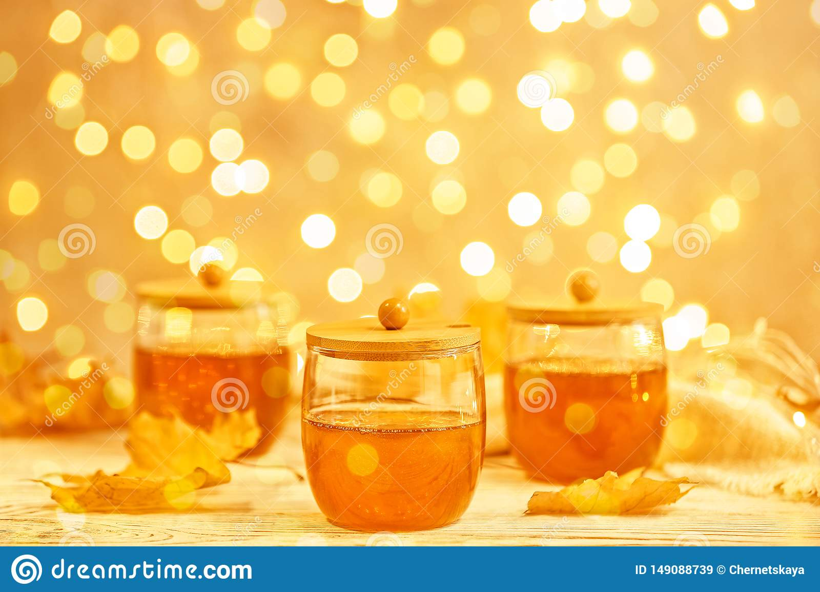 Glass jars with sweet honey on table against blurred lights