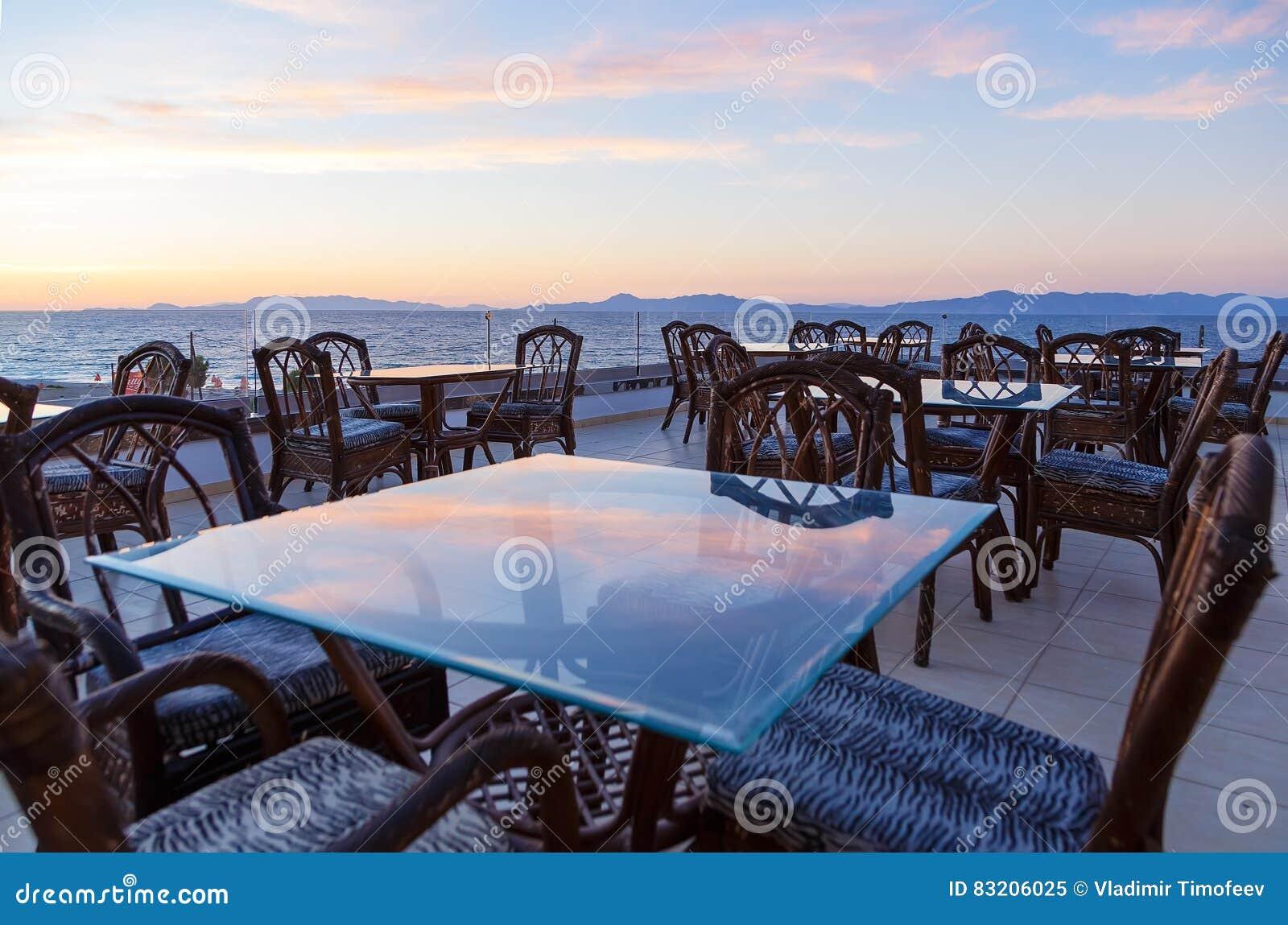 Glass kafétabeller på taket av semesterorten med siktshavet och härlig solnedgång