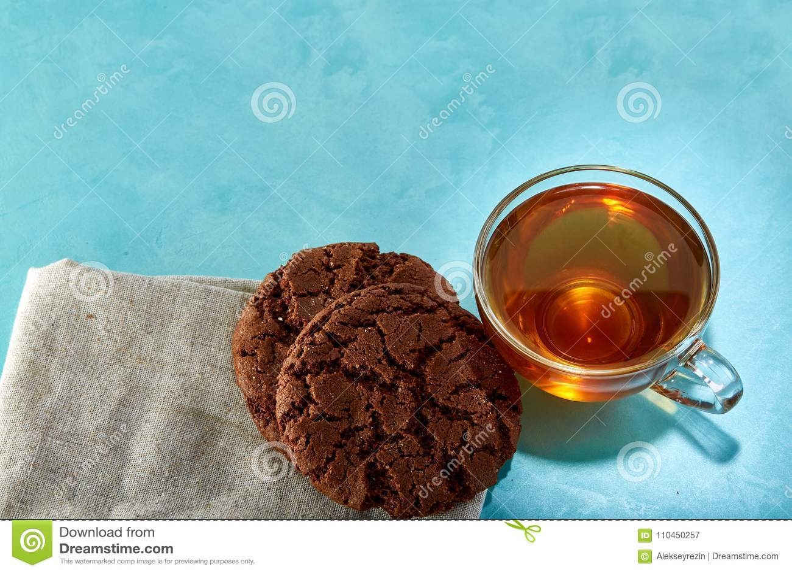 Glass kopp te- och chokladkakanärbild på blå bakgrund