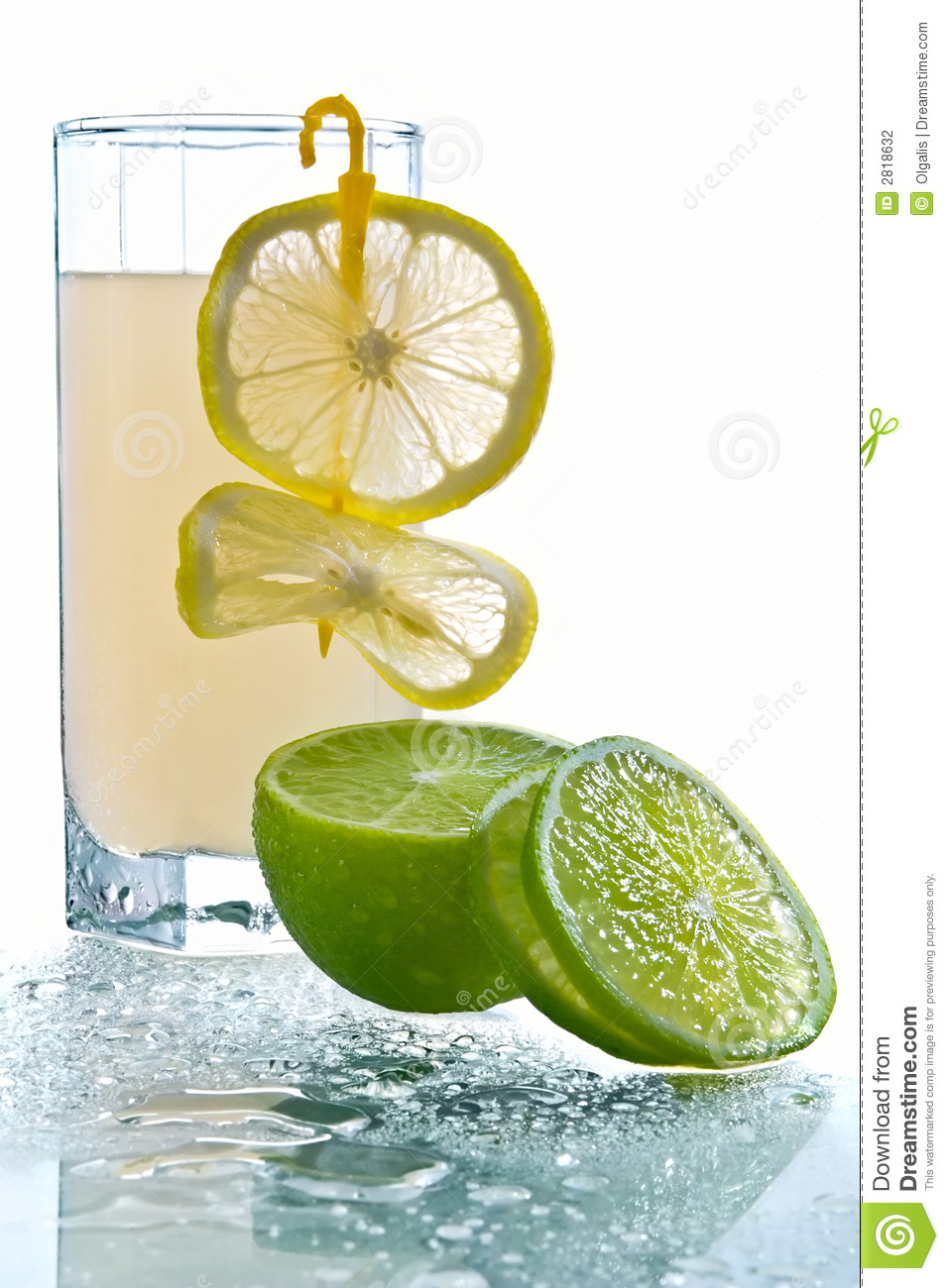 Glass of lemonade in an environment of fresh lemon decoration and lime