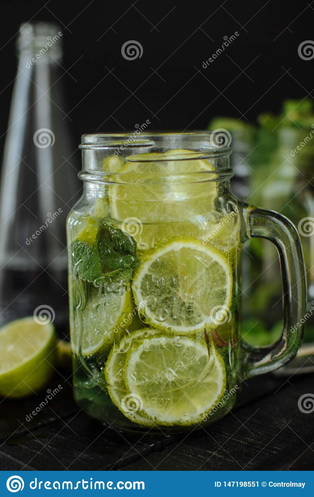 A glass of lemonade with sliced lime and lemon in a mug on a black background.