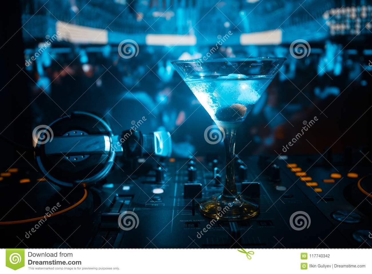 Glass with martini with olive inside on dj controller in night club. Dj Console with club drink at music party in nightclub with d