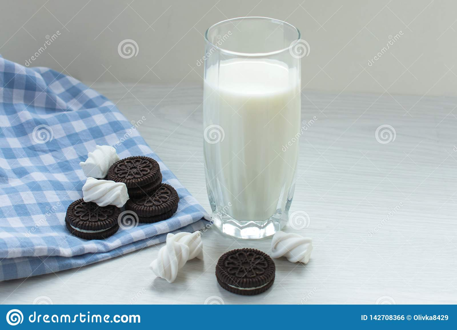 A glass of milk with chocolate chip cookies and a march of melow on a white table