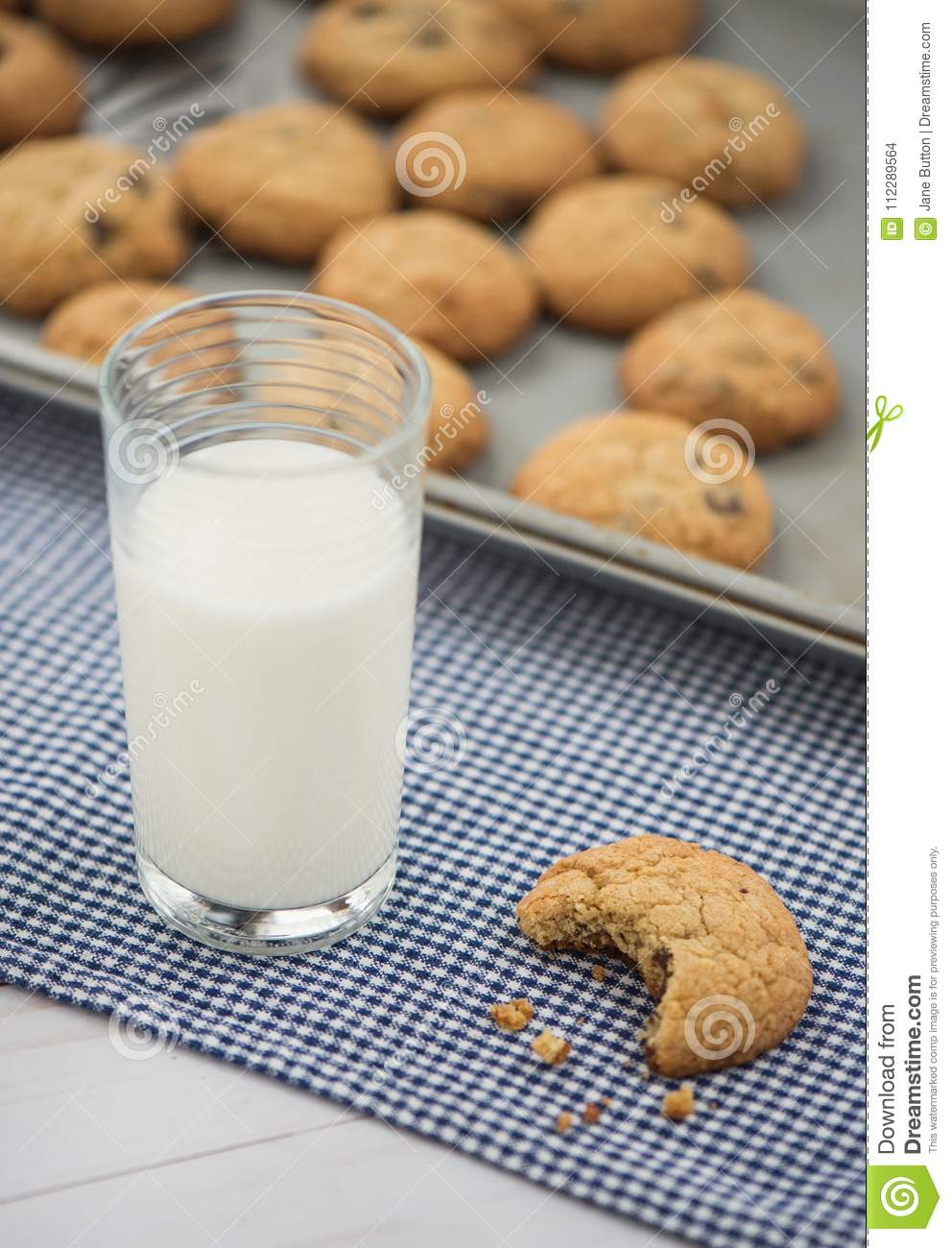A glass of milk and a cookie with a bite taken out of it sit on