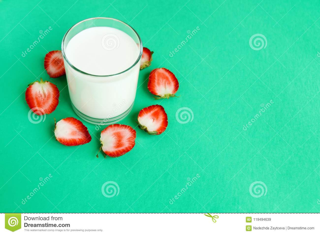 Glass of milk and halves of strawberry around on a turquoise background, top view.
