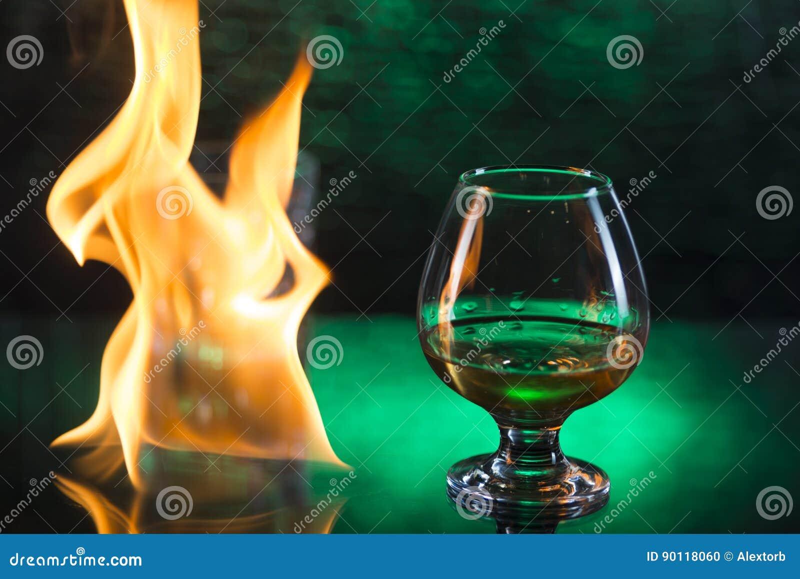 Glass nolla-whisky med is och vinglaset av konjak och brand flammar på grön bokehbakgrund