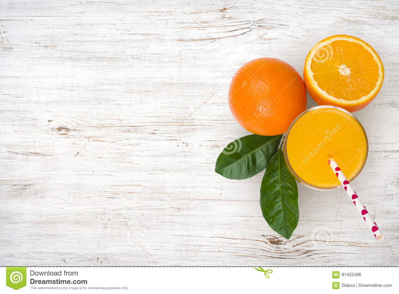 Glass of orange juice and fruits on vintage wooden background