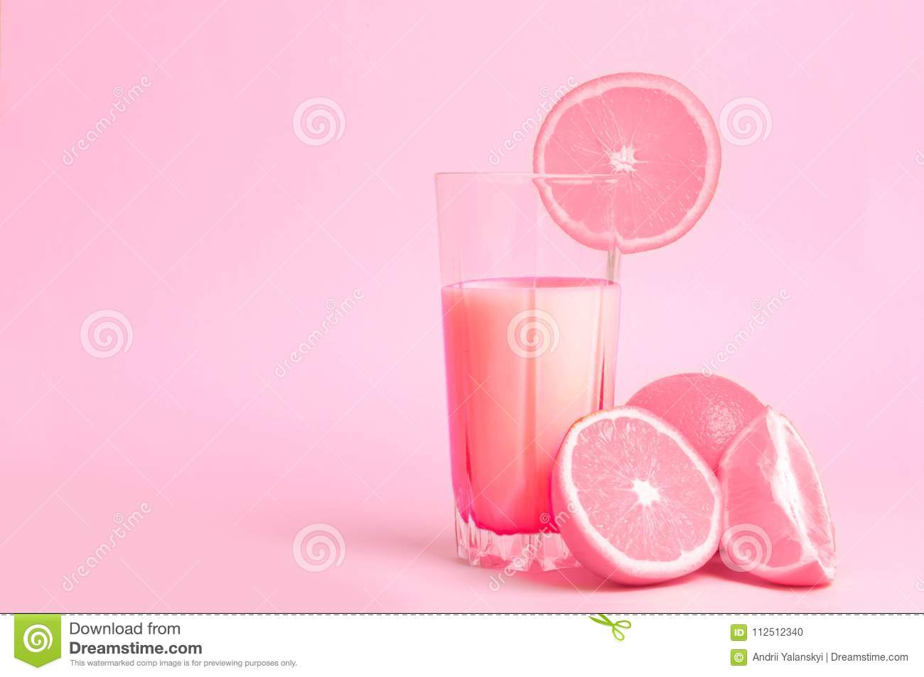 A glass with pink orange juice with the cut oranges on a pink background. Juicy color scale, pin up, pop up styles. Food for break
