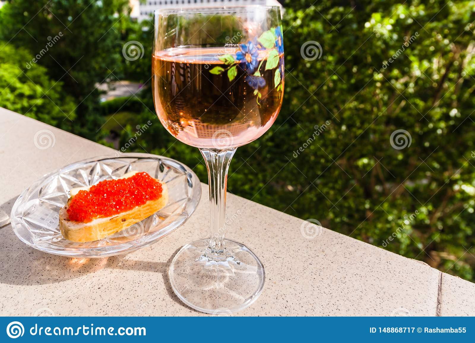 a glass of pink wine and bread with red caviar on the parapet