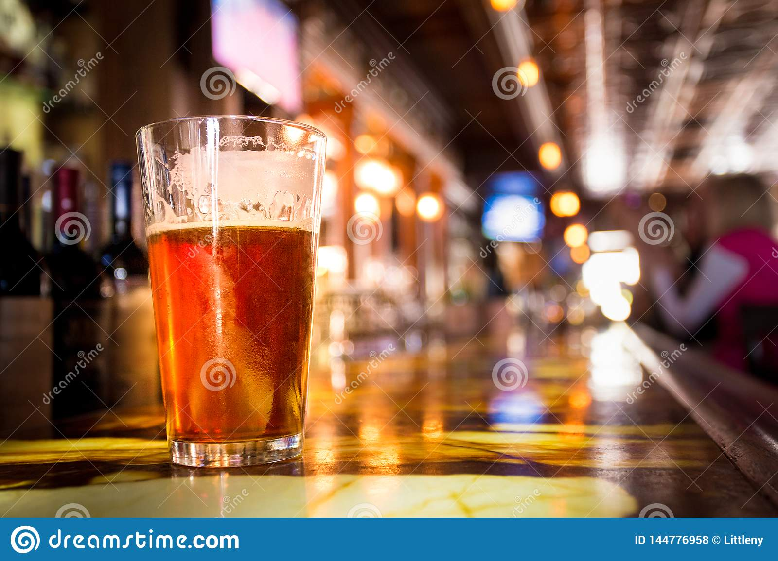 Glass Pint of amber beer with colorful blur of bar