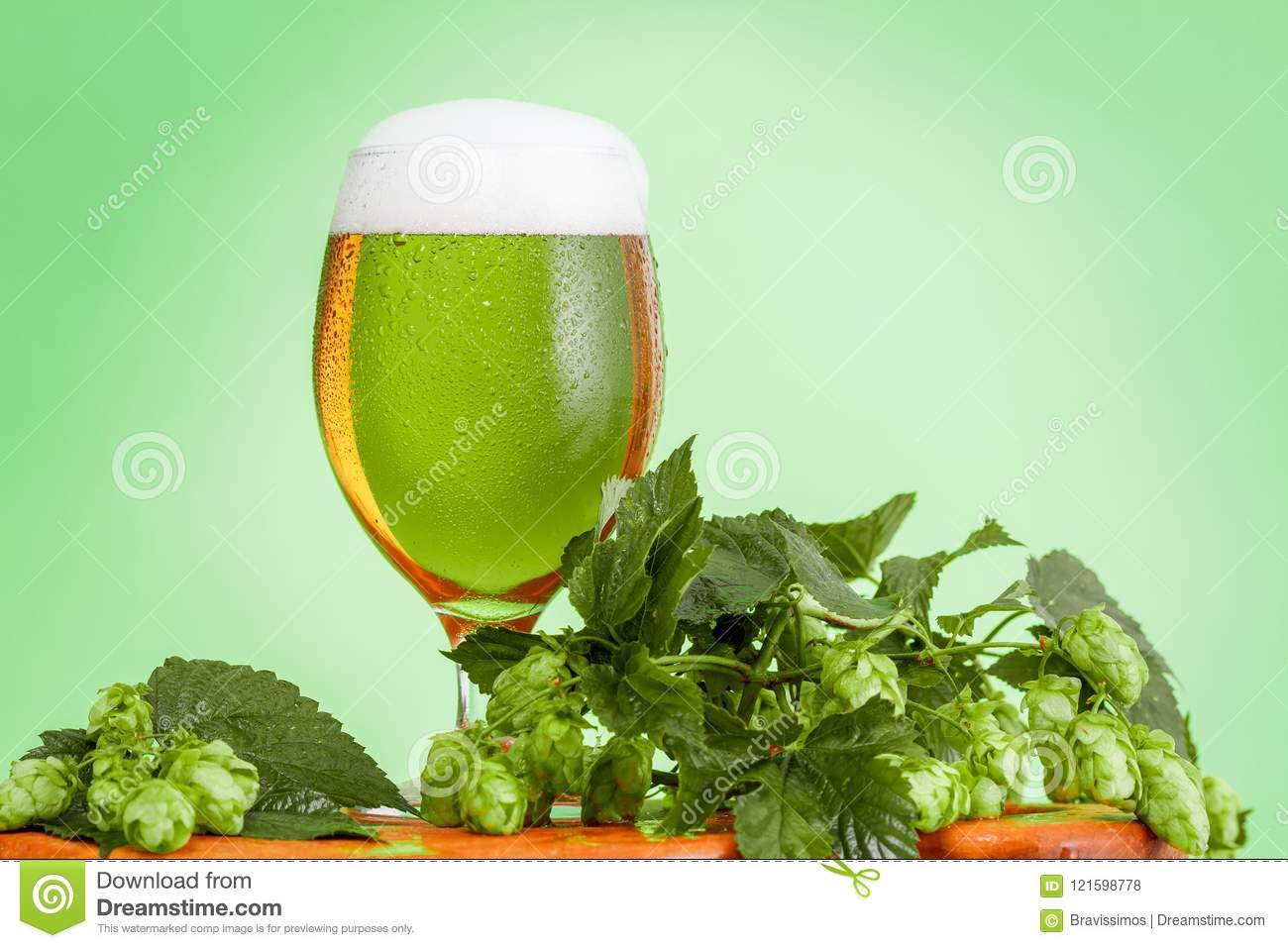 Glass Pint of beer, homemade ingredients for beer on green