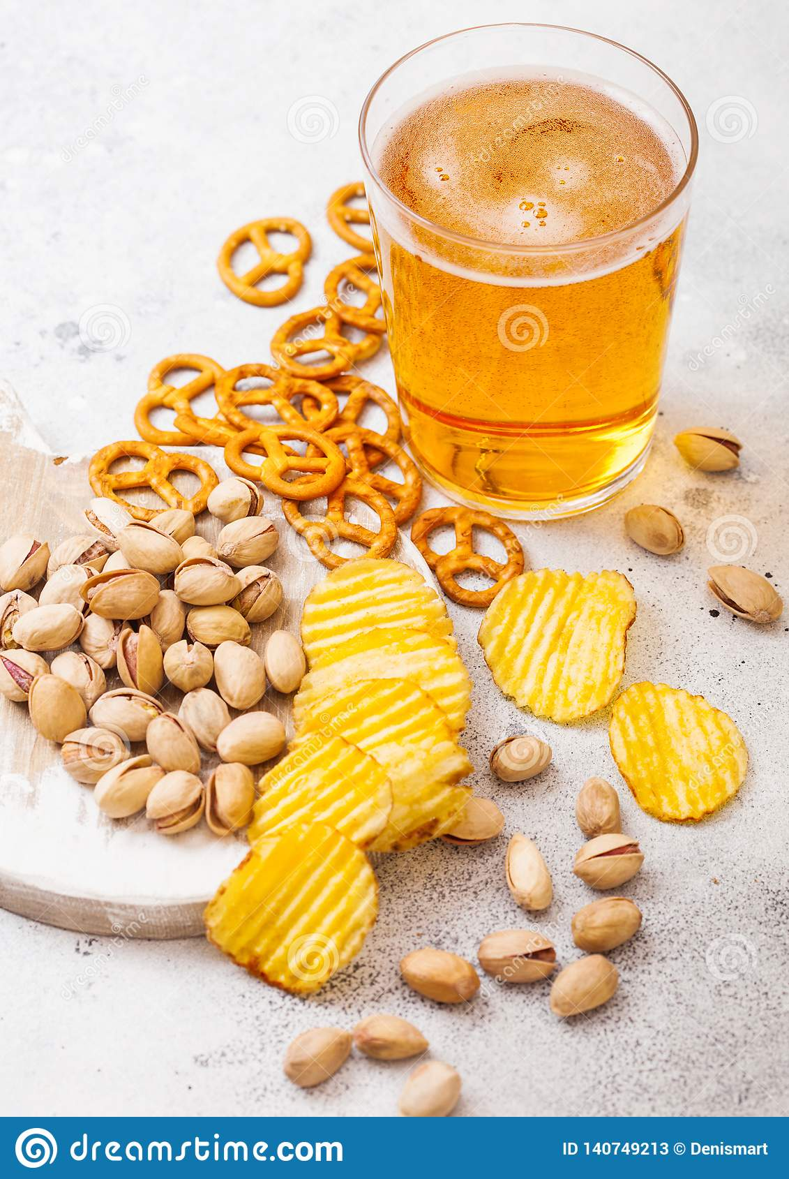 Glass pint of craft lager beer with snack on stone kitchen table background. Pretzel and crisps and pistachio on roud wooden board