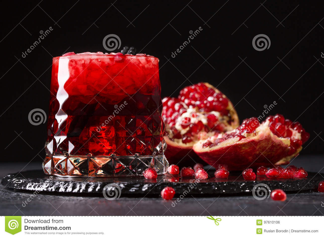 A glass of a pomegranate drink with ice and cut garnet on a black background. Fresh and organic summer cocktails.